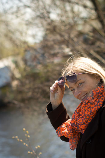 Portrait of woman wearing sunglasses looking at lake