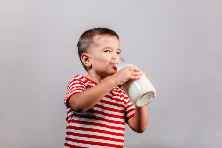 Portrait of young boy holding bottle of milk isolated over gray background - studio shot. Child drinking milk from glass bottle against grey background. Child Striped One Person Drink Drinking Boy Milk Bottle Red Color T-shirt 3-5 Years Grey Gray Background Isolated Studio Shot Indoor Caucasian Horizontal Helth Healthy Eating Dairy Portrait Glass Holding