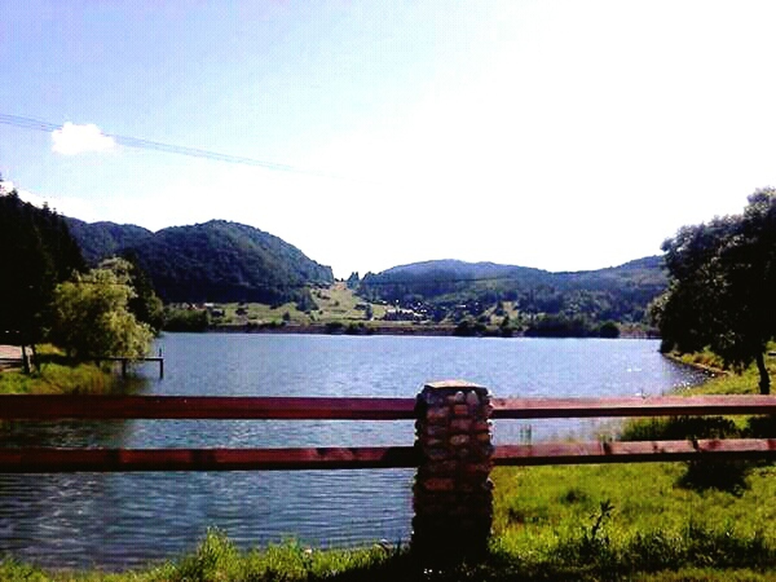 mountain, water, mountain range, lake, tranquil scene, tranquility, scenics, beauty in nature, nature, sky, blue, river, clear sky, tree, idyllic, railing, landscape, countryside, day, non-urban scene