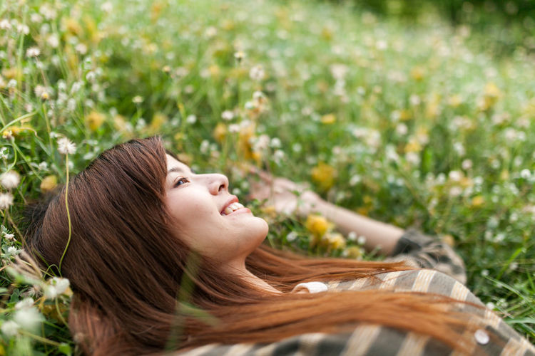 High angle view of carefree young woman lying down on grassy field