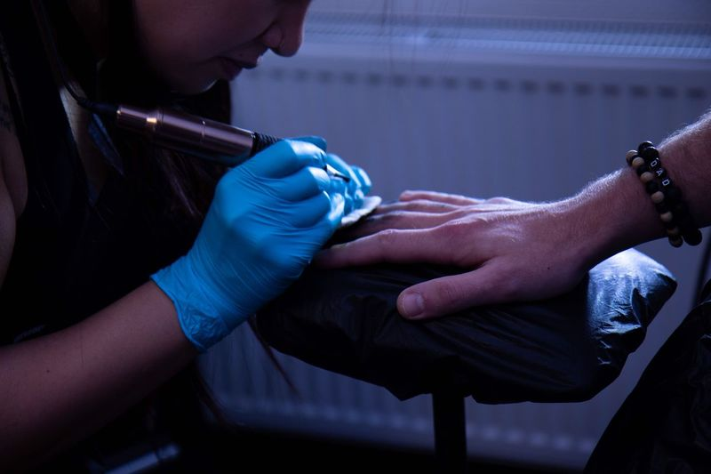 Woman tattooing on man hand at studio