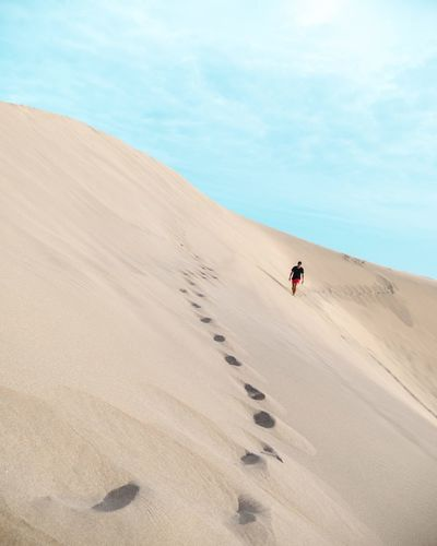 Man walking on sand dune against sky