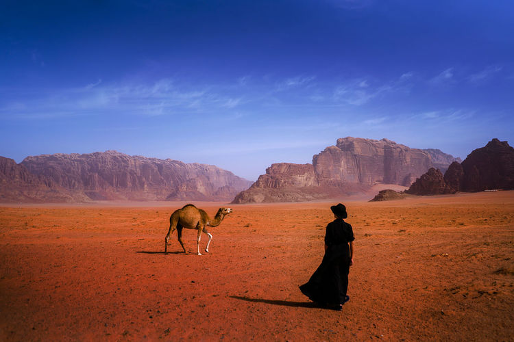 Rear view of woman standing on land with camel against mountains and sky