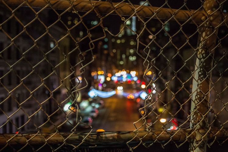 Illuminated city seen through chainlink fence at night