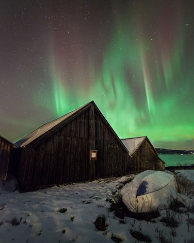 Wooden Houses By Snowcapped Field Against Aurora Borealis In Sky