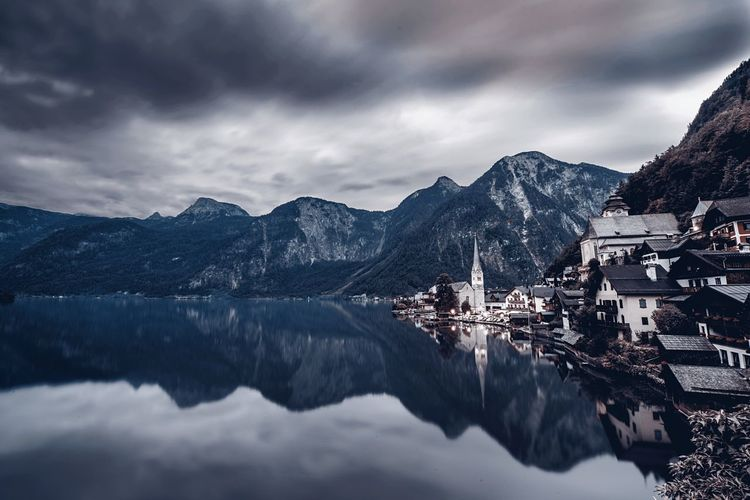 Scenic View Of Hallstatt And Mountains Reflection In Hallstatter See