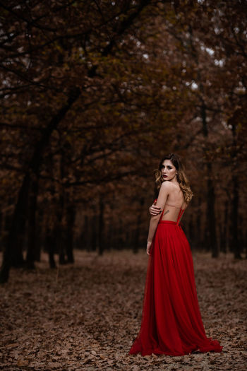 Portrait of woman with red umbrella in the forest