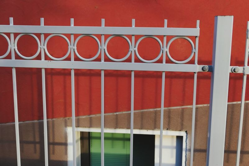 Metal fence against red wall