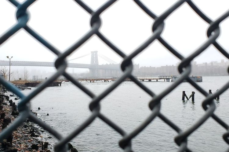 Williamsburg bridge from behind a fence from domino park
