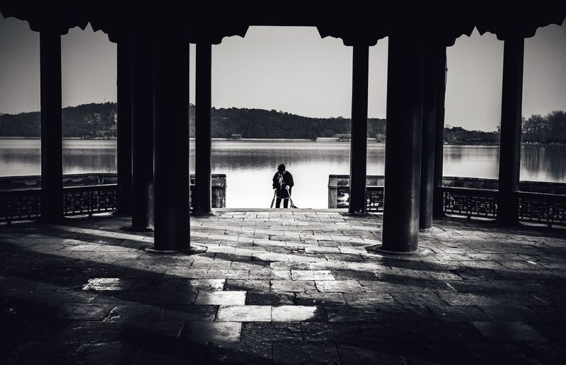 Rear view of silhouette man standing by river against sky