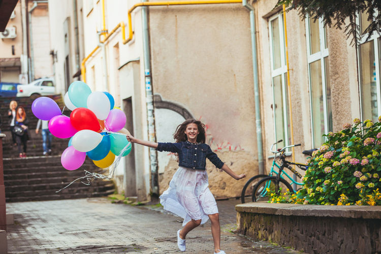 Full length of woman holding balloons