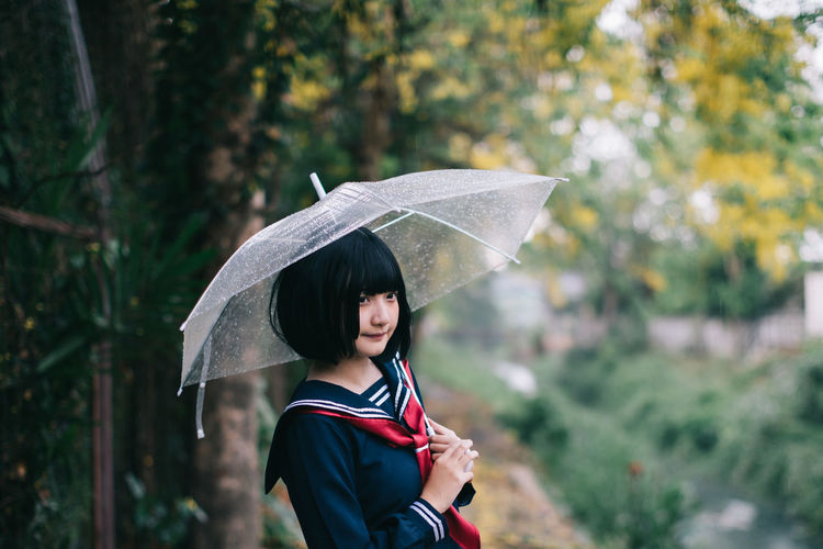 Woman holding umbrella standing in rain during rainy season
