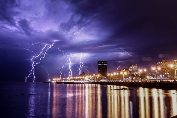 Lightning over illuminated city against sky at night