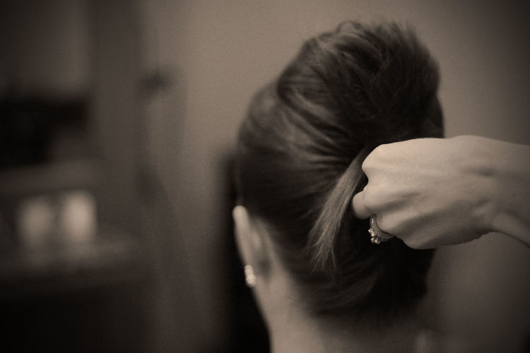 Cropped image of hands making hair bun of woman
