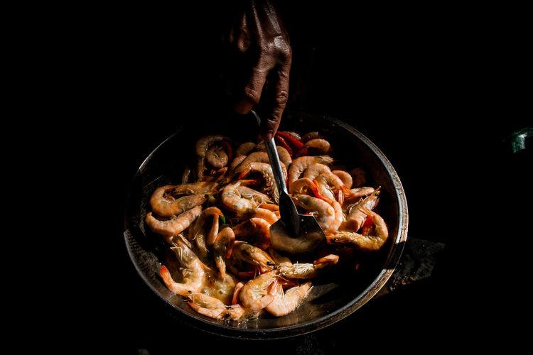 Cropped hand preparing shrimp against black background