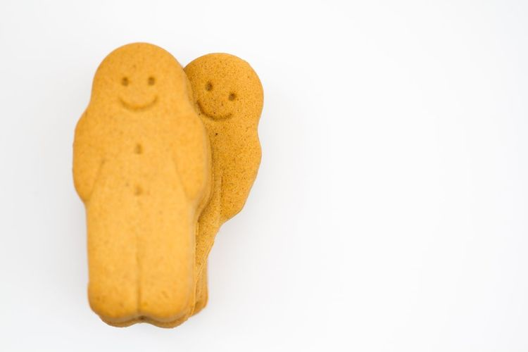 A pile of smiling gingerbread men with a cheeky person peeking out from the rest and on an isolated white background. Gingerbreadman Gingerbread Man Biscuit Biscuits Children Baking Children Cooking White Background Smiling Happy Cheeky Individual Personality  Gingerbread Men Gingerbread Person Baking Cookies Isolated White Background Individuality
