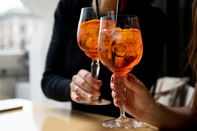 Woman toasting with aperol spritz cocktails Alcohol Aperol Spritz Wineglass Glass Drink Refreshment Orange Color Orange - Fruit Restaurant Togetherness Real People Food And Drink Holding Wine Business Lifestyles Midsection Celebration Event Celebration Celebratory Toast Cocktail Friendship Wine Glass Summertime Toasting Hand People Copy Space Alcoholic Drink Summer Dogs Aperol Indoors