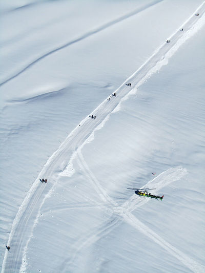 Aerial view of helicopter and people on snow covered field