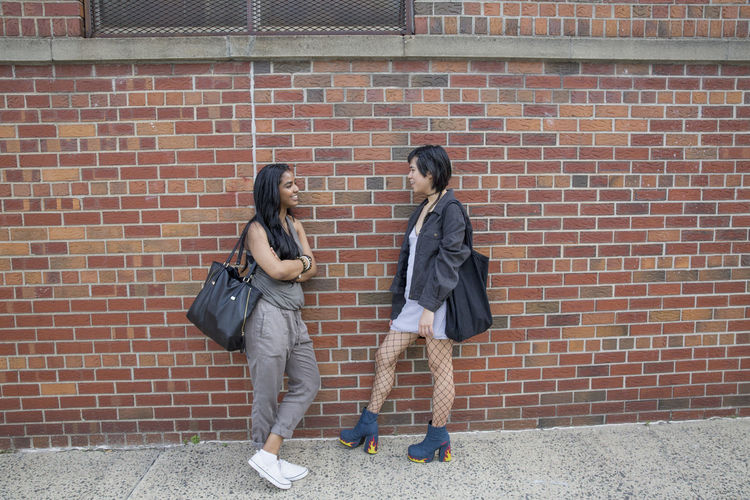 Friends standing against brick wall