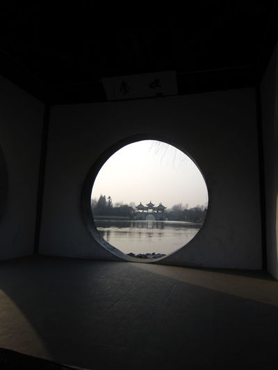 River seen through circle shaped window at dusk