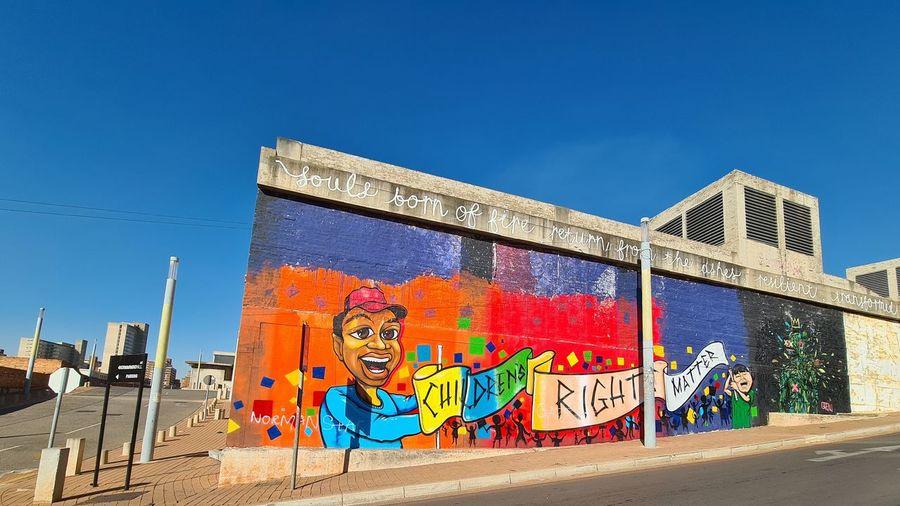 Graffiti on wall against blue sky