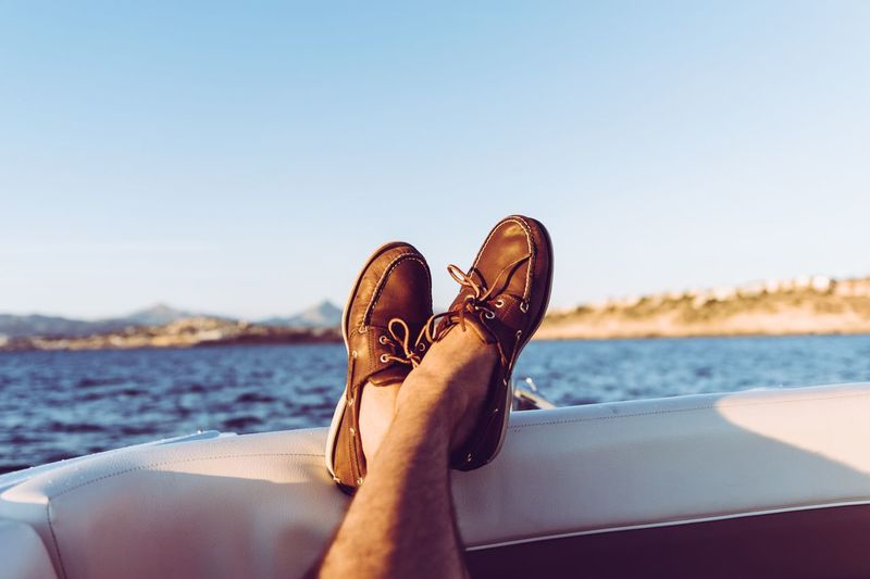 Low section of man wearing shoes resting on boat in sea