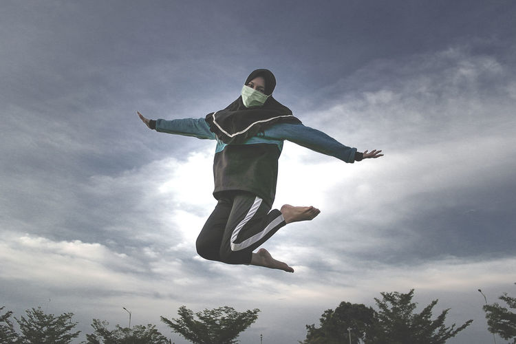 Low angle view portrait of woman jumping against sky