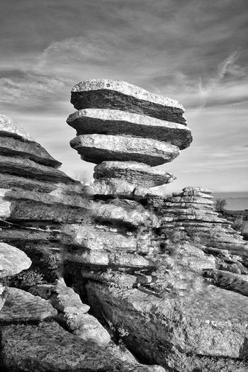 Stack of rocks on shore against sky