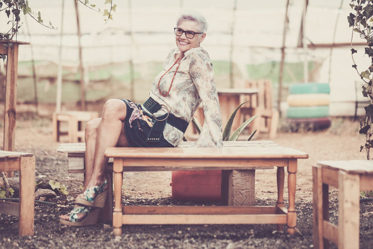 Happy mature woman sitting on wooden bench at park