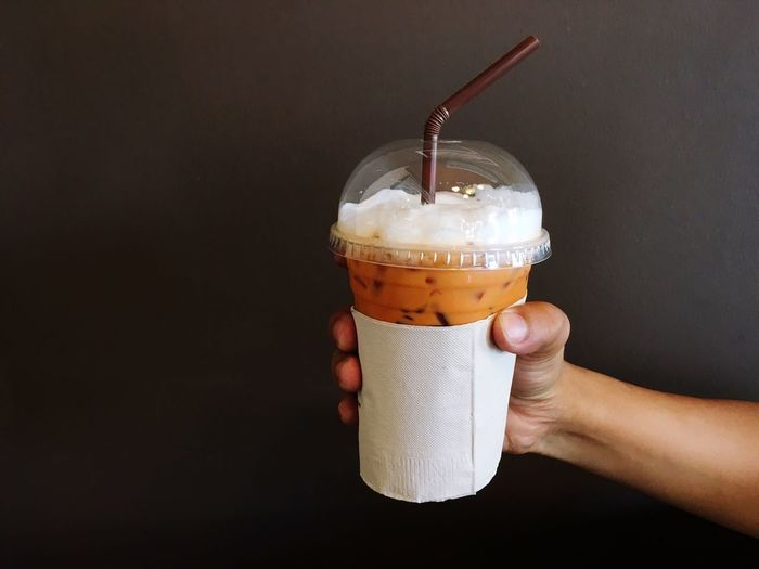 Close-up of hand holding iced coffee against black background