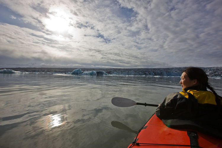 Rear view of man in sea against sky during winter