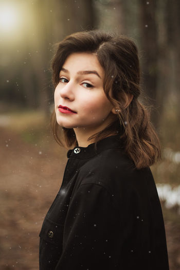 Portrait of beautiful young woman standing outdoors
