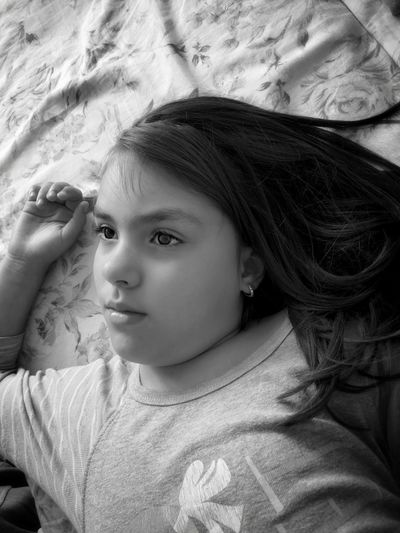 High angle portrait of girl lying on bed