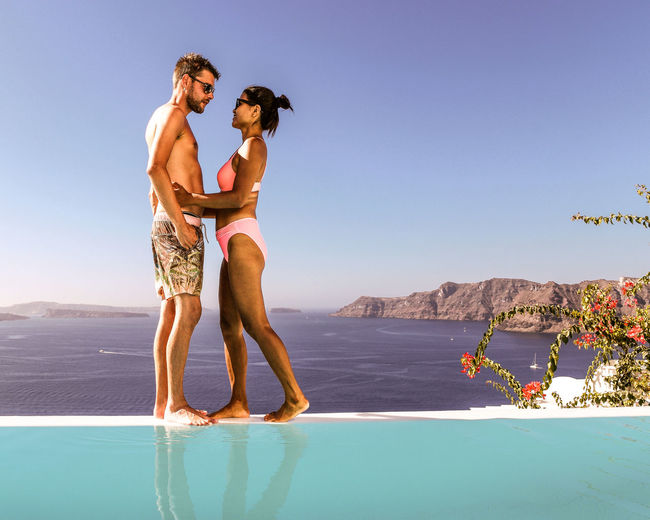 Full length of young couple standing by infinity pool at sea against clear sky