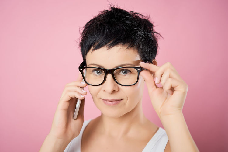 Portrait Colored Background Studio Shot Eyeglasses  One Person Glasses Headshot Looking At Camera Young Adult Pink Background Indoors  Adult Pink Color Human Body Part Close-up Beauty Hair Front View Beautiful Woman Body Part Hairstyle Human Face Hand Human Hair