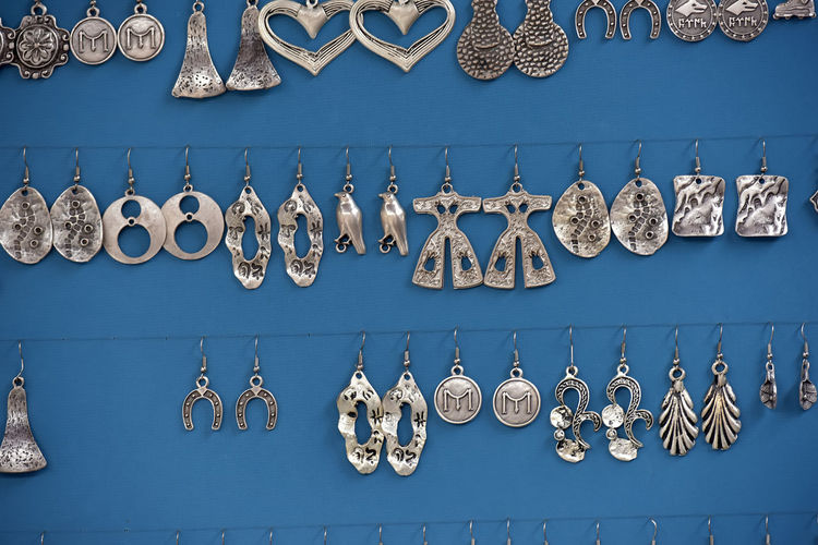 Earrings against blue wall