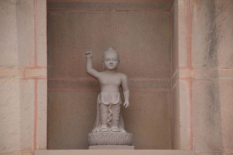 Statue of buddha against wall