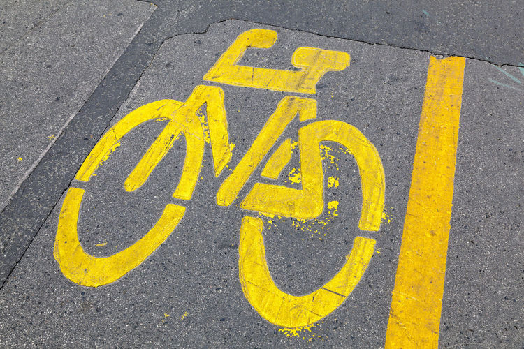 Close-up of yellow arrow symbol on road in city