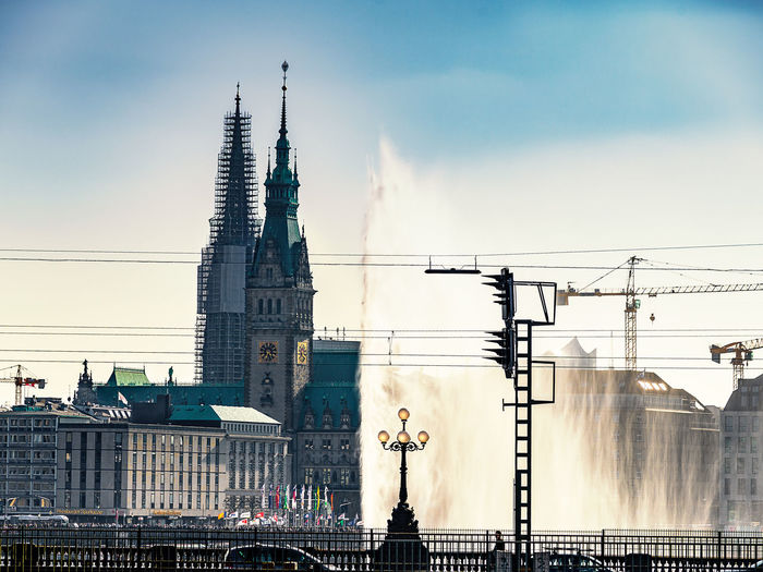 Low angle view of water fountain against hamburg rathaus