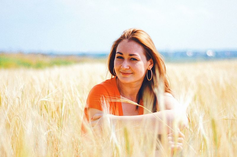 Portrait Of Smiling Woman Sitting On Wheat Field
