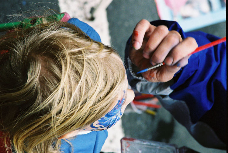 Cropped image of hand painting child face