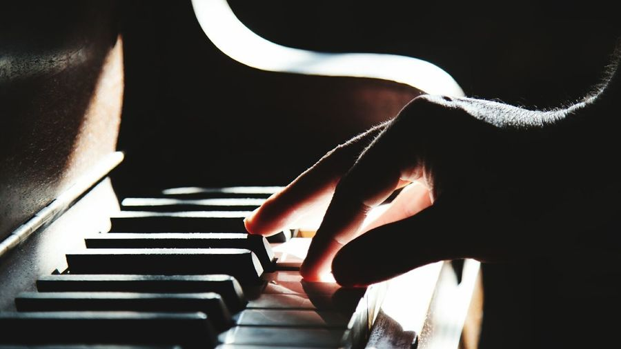 Close-Up Of Hand Playing Piano In Darkroom