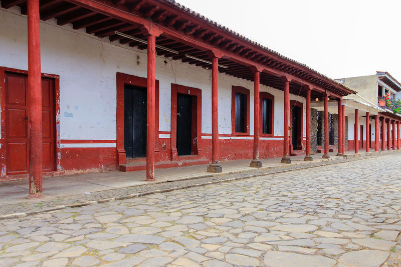 A public plaza in Tzintzuntzan, Michoacan, Mexico Architectural Column Architecture Building Exterior Built Structure Clear Sky Cobblestone Colonnade Day Exterior In A Row Mexico Multi Colored No People Outdoors Paving Stone Plaza Red Red Color Sky Tourism Town Square Tzintzuntzan