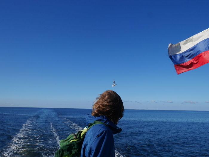 Side view of man standing by russian flag against sea