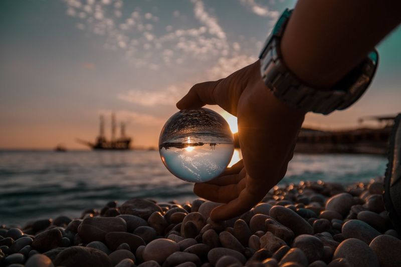 Close-Up Of Hand Holding Crystal Ball At Beach During Sunset