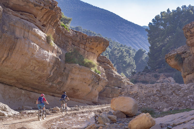 Mountain Rock Real People Leisure Activity Adventure Rock Formation Activity Lifestyles Outdoors Bikers Mountain Bikers Holiday Vacation Man And Woman Couple Biking Mountain Biking Red Rocks  Golden Hour Light Canyon Husband And Wife Morocco Pedalling Trail