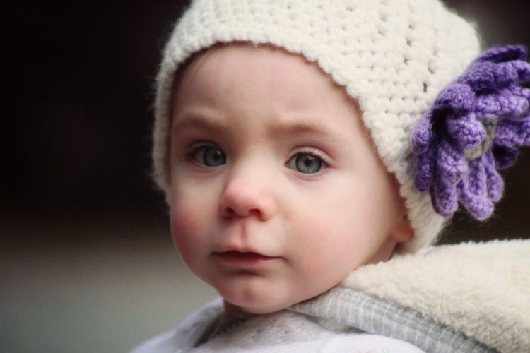 Close-up portrait of cute baby girl wearing knit hat
