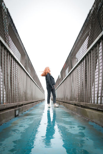 Girl standing on wet footbridge against clear sky