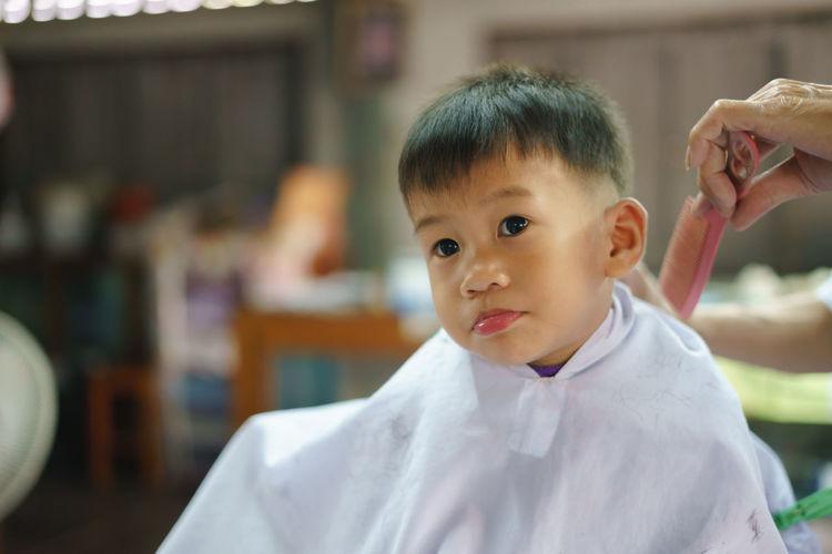 Cute boy sitting at barber shop