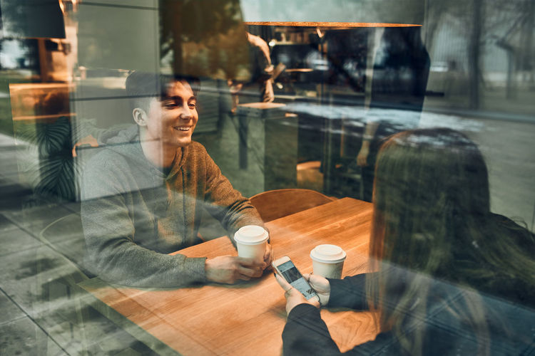 Friends having chat, talking, drinking coffee, sitting in cafe. people relaxing having break in cafe
